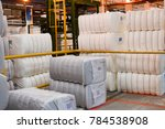 Small photo of Warehouse with a bunch of huge, white, rectangular bags with acrylic fiber.