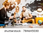 Small photo of Young lovely couple sitting with manager at the travel agency office prepairing for a summer vacation