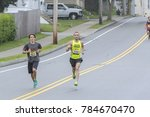 Small photo of Fairhaven, Massachusetss, USA - June 18, 2017: Runners flying down hill during Father's Day Road Race