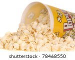 Container of delicious movie popcorn with popcorn spilling out - stock photo