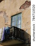 Small photo of stucco and exposed brick, dilapidated balcony in russia