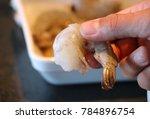 man holding shrimp in hand  | Shutterstock . vector #784896754
