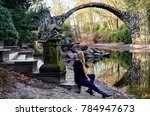 long hair blond woman sitting on the stairs at bridge rakottsbryuke in germany during winter time