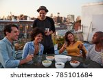 Small photo of Six adult friends enjoying a party on a rooftop, close up