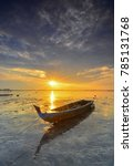 Small photo of Traditional boat at sunrise on the beach Ocarina island Batam