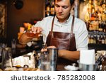 young barman in a brown leather ... | Shutterstock . vector #785282008