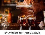 Stock photo bartender pouring fresh alcoholic drink into the glasses with ice cubes on the bar counter 785282026