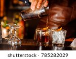 Stock photo barman pouring fresh alcoholic drink into the glasses with ice cubes on the bar counter 785282029