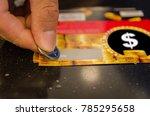 a human hand using a coin on a... | Shutterstock . vector #785295658