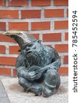 Small photo of WROCLAW - POLAND, JUNE 12, 2017 : Wroclaw dwarf, small fairy-tale bronze figurine on the side walk, musician. There are over 350 dwarfs spread all over the city, they are a big tourist attraction