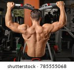 Small photo of Young man training on exercise machine in gym