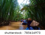 My Tho, Vietnam: Tourist at Mekong River Delta jungle cruise with unidentified craftman and fisherman rowing boats on flooding muddy lotus field in Mekong delta into Ho Chi minh city