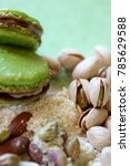 Small photo of on a pastel green background, in natural light, two pistachio macaroons surrounded by almond powder, shell pistachios and whole almonds