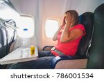 Small photo of Fear of flying woman in plane airsick with stress headache and motion sickness or airsickness. Focus on bottle and tablets.