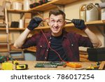 Small photo of Multimeter for electrician. Crazy aggressive batty mad fun young man in plaid shirt, digital electronic engineer repairing, soldering computer PC motherboard in workshop at wooden table with tools