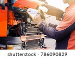 Truck inspection and safety. Truck driver is checking truck engine. - stock photo