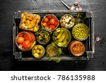 Small photo of Preserves vegetables in glass jars in an old box. On the black chalkboard.