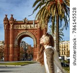 Small photo of in Barcelona for a perfect winter. relaxed trendy fashion-monger in earmuffs near Arc de Triomf in Barcelona, Spain sitting on a parapet