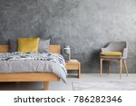 Stock photo grey chair and lamp on wooden nightstand in dark bedroom with concrete wall and yellow pillow on bed 786282346