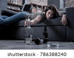Small photo of I need this drink. Selective focus of a half empty vodka bottle being taken by a drunken young woman while having a hangover
