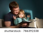 father reading a story to his...   Shutterstock . vector #786392338