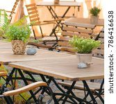 Small photo of Wooden chairs and tables at outdoor area of restaurant, decorated with potted plants; Outdoor gastronomy; Table number thirty-six and thirty-seven