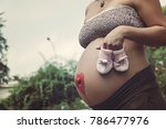 future mom with baby shoes | Shutterstock . vector #786477976