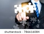 Small photo of Mergers and acquisition concept with consultant touching icons of puzzle pieces representing the merging of two companies or joint venture, partnership