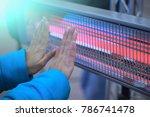 a woman in a blue jacket warmes ... | Shutterstock . vector #786741478