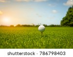 Golf ball on tee in green grass ...
