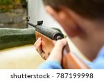 Small photo of A boy shooting from an air rifle to a target. A boy with a gun in his hand. Shooting training from a gun. Dangerous game of little boy.