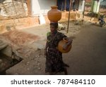 Small photo of India, Tamilnadu - February 14, 2016: Indian life. Woman with clay jugs (amphora, one on head), water carrier