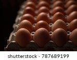 Small photo of High angle shot of eggs on an egg carton over dark background stressing subject in dimension of amount, shape, color, and signification