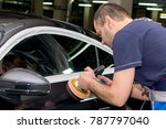 a man polishes a black car with ... | Shutterstock . vector #787797040