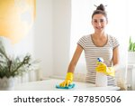 Portrait of the young smiling woman in yellow gloves who holding rag and detergent and wiping a table in the room