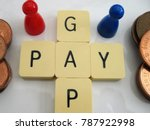 Small photo of Gender pay gap depiction with larger coins for blue (male), smaller coins for red (female)