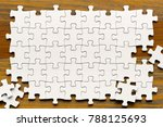White Puzzle Pieces On Wood...