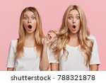 Small photo of Stupefied female models with appealing appearance look with great surprisment at camera, being afraid of something awful, stare in stupor, isolated over pink background. People and reaction concept