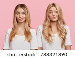 Small photo of Puzzled blonde two females stand close to each other, curve lips, being uncertain about making decision, isolated over pink background. Beautiful sisters dressed casually don`t know what to do