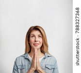 Small photo of Hopeful attractive fashionable woman keeps palms pressed together, looks with big hope upwards, believes or asks for good luck. Beautiful female prayer poses aginst white concrete studio wall