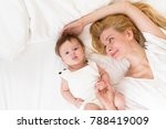 Small photo of Portrait of beautiful young mom playing with her 4 months old baby girl in light bedroom, top view. Smiling and laughing mother with babygirl