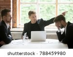 Small photo of Angry boss firing unprofessional employee with hand gesture at office meeting, dissatisfied ceo dismissing male incompetent manager for poor performance or bad work result sitting at conference table