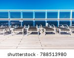 Cruise Ship Sea Travel Concept with Wooden Deckchairs on the Open Deck of the Ship. - stock photo
