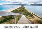 Looking down a staircase at a very narrow isthmus with a road along it on Bruny Island, Tasmania.