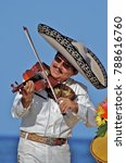 Small photo of Puerto Vallarta, Jalisco / Mexico - 10/01/2016: Mariachi Plays a ?Violin? for Beach Audience Wearing Traditional White Suit, Charro Shirt, Sombrero Hat and Mexican Bow Tie