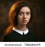 Stock photo dramatic portrait of a beautiful lonely girl with freckles isolated on a dark background in studio 788686699