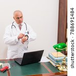 Small photo of Aback doctor in his studio, uses a smartwacth front of his laptop. Use new technologies. In his professional studio, he is sitting at antique desk, and a green lamp shade of green.
