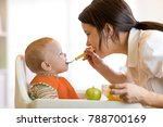 mother giving fruit puree to... | Shutterstock . vector #788700169