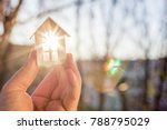 Small photo of House in hand in the rays of the sun. The concept of protection of property.