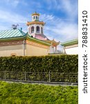 Small photo of A Chinese-style pavilion with a dragon on the roof and a green fence made of thuya in the Alexander Park in Pushkin in St. Petersburg in the early spring in early May on a clear, sunny day